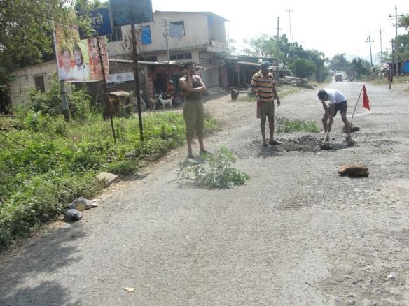 Men repairing road in India
